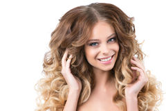 Portrait of beautiful young smiling girl with luxuriant hair curling. Royalty Free Stock Photos