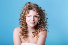 Portrait of beautiful young smiling girl with luxuriant hair curling. Health and Beauty. Royalty Free Stock Photo