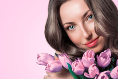 Portrait of a beautiful young smiling woman with a bouquet of flowers. Female face close Royalty Free Stock Photography