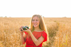 Portrait of beautiful young smiling woman with camera in the field Royalty Free Stock Photography
