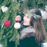 Portrait of beautiful young smiling woman decorating Christmas tree outdoors on a cold winter day. stock images