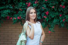 Portrait of beautiful young smiling woman, holding leather hand bag Stock Photo