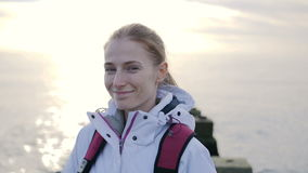 Portrait of beautiful young smiling woman in jacket with backpack on pier with sea on a background stock video footage