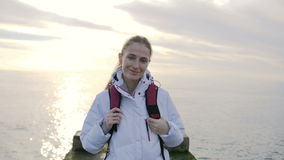 Portrait of beautiful young smiling woman in jacket with backpack on pier with sea on a background stock footage