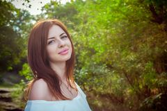 Portrait of beautiful young smiling woman with long red hair. Wearing elegant white top in a forest with green trees on a sunny summer day Royalty Free Stock Photos