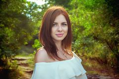 Portrait of beautiful young smiling woman with long red hair. Wearing elegant white top in a forest with green trees on a sunny summer day Royalty Free Stock Images
