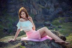 Portrait of beautiful young smiling woman sitting barefoot on a cliff royalty free stock photos