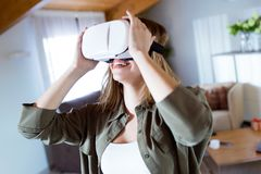 Beautiful young smiling woman using virtual reality headset at home. Royalty Free Stock Images