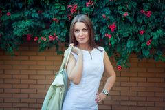 Portrait of beautiful young smiling woman, wearing elegant white dress, holding  leather hand bag, Stock Photo