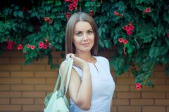 Portrait of beautiful young smiling woman, holding leather hand bag Stock Photography