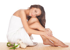 Spa woman. Portrait of beautiful young spa woman with healthy skin sitting and hugging her legs. Isolated on white background Stock Photo