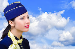 Portrait of a beautiful young stewardess. In profile on the sky background Stock Photography