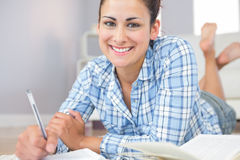 Portrait of beautiful young student doing assignments lying on the floor Royalty Free Stock Image