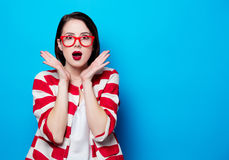 Portrait of the beautiful young surprised woman. On the blue background Royalty Free Stock Photo