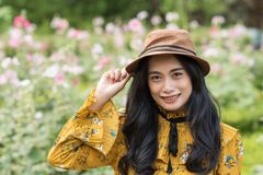 Bohemian Asian girl in rose garden. Portrait of beautiful young tan Bohemian Asian girl in boho style outfit and hat in rose flower garden on summer day Stock Photo