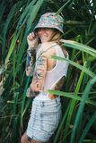 Portrait of beautiful young tattooed smiling woman standing in green leafy bush Stock Photo