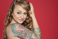 Portrait of beautiful young tattooed woman over colored background stock image