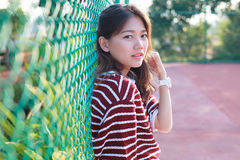 Portrait of beautiful young teen woman leaning steel net fence a Stock Images
