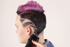 Portrait of a beautiful young teenager with a beautiful creative hairstyle, hair painted in pink. Hairdresser cuts hair with clipper. Portrait of a beautiful stock photo