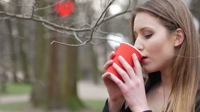 Portrait of beautiful young urban fashion girl in autumn park drinking cup of takeaway coffee.  stock video footage