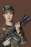 Portrait of beautiful young US Marine Corps soldier with M4 assault rifle over brown background Stock Photos
