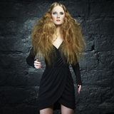 Portrait of a beautiful young woman. With curly red hair. Fashion & Beauty Stock Image