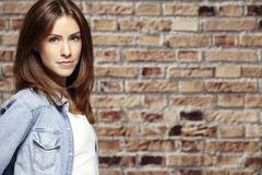 Portrait of a beautiful young woman, against brick wall. Portrait of a young woman in front of a brick wall Royalty Free Stock Photo