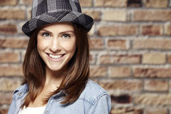 Portrait of a beautiful young woman, against brick wall. Portrait of a young woman in front of a brick wall, wearing a hat Royalty Free Stock Image