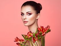 Portrait of beautiful young woman with Alstroemeria flowers stock images