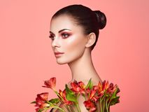 Portrait of beautiful young woman with Alstroemeria flowers royalty free stock photos