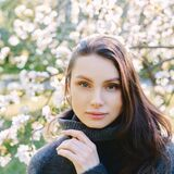 Portrait of beautiful young woman in apple trees blooming park on a sunny day. Dark hair. Happiness concept.