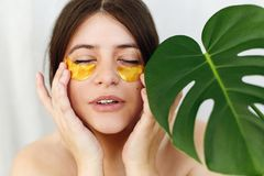 Portrait of beautiful young woman applying golden eye patches on fresh soft skin at green palm leaf on white background. Happy royalty free stock images