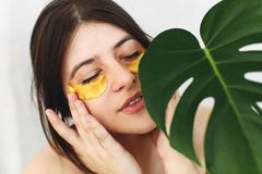 Portrait of beautiful young woman applying golden eye patches on fresh soft skin at green palm leaf on white. Happy girl with royalty free stock image