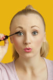 Portrait of a beautiful young woman applying mascara over yellow background Royalty Free Stock Images
