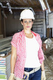 Portrait of beautiful young woman architect wearing hardhat at construction site Stock Photos