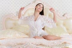 Portrait of beautiful young woman awaking on soft beige bed at morning. Beautiful young woman awaking on soft beige bed at morning royalty free stock photography