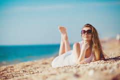 Portrait of a beautiful young woman on the beach in the sand Royalty Free Stock Photos