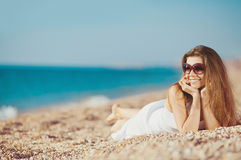 Portrait of a beautiful young woman on the beach in the sand Stock Photo