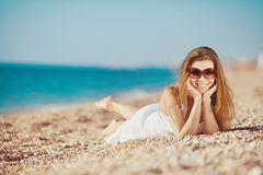 Portrait of a beautiful young woman on the beach in the sand Royalty Free Stock Photo