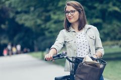 Portrait of young woman with bicycle in park Royalty Free Stock Image