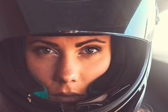 Closeup portrait of beautiful young woman biker wearing a black helmet with an open visor. Portrait of beautiful young woman biker wearing a black helmet with royalty free stock image