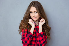 Portrait of a beautiful young woman biting her lips. Portrait of a beautiful young woman with curly hair in plaid shirt biting her lips stock images