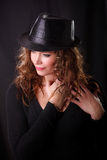 Portrait of beautiful young woman in black hat. Glamour Portrait of beautiful young woman in black hat and brown long ringlets hair stock image