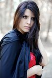 Portrait of beautiful young woman with black mantle in magic woods Royalty Free Stock Photos