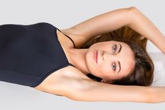 Portrait of a beautiful young woman in a black swimsuit. Photo indoors Royalty Free Stock Photo
