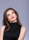 Portrait of beautiful young woman in a black turtleneck. To think o something or to choose. Brunette. The red lipstick. Grey background royalty free stock images