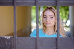 Portrait of beautiful young woman with blond hair and long eyelashes, behind the grid. prison concept. Portrait of beautiful young woman with blond hair and long royalty free stock image