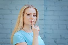 Portrait of beautiful young woman with blond hair and long eyelashes, making silence gesture. Portrait of beautiful young woman with long eyelashes in the city royalty free stock image