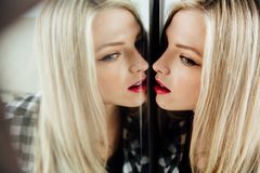 Portrait of beautiful young woman blonde girl and her reflection in mirror. royalty free stock photography