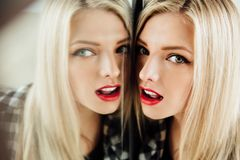 Portrait of beautiful young woman blonde girl and her reflection in mirror. stock photos